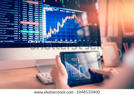 Businesswoman trading stocks with tablet and graph Analysis in desktop computer Royalty-Free Stock Photo #1048533400