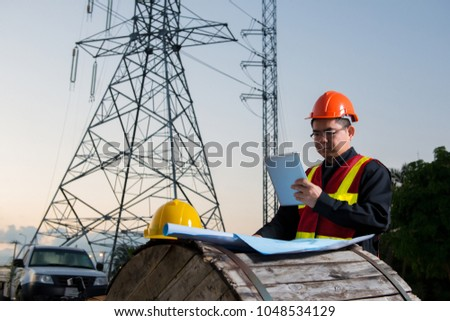 Electrical engineer working. Electrician holding tablet at high voltage power pylon against blue sky #1048534129
