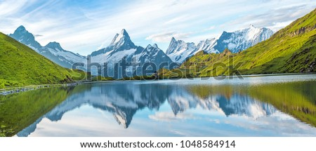 A magical panorama landscape with a lake in the mountains in the Swiss Alps, Europe. Wetterhorn, Schreckhorn, Finsteraarhorn et Bachsee. ( relaxation, harmony, anti-stress - concept).  Royalty-Free Stock Photo #1048584914