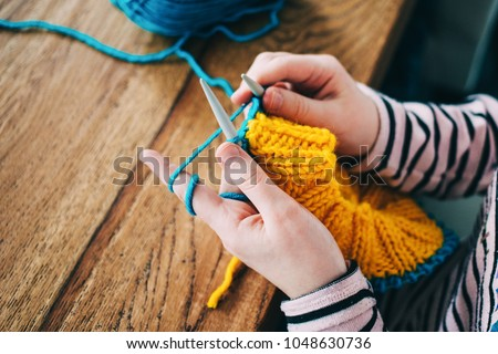 Young girl knitting a circle scarf with yellow and blue coloured yarn. Sitting at the wooden table, close up of the knitting needles. #1048630736