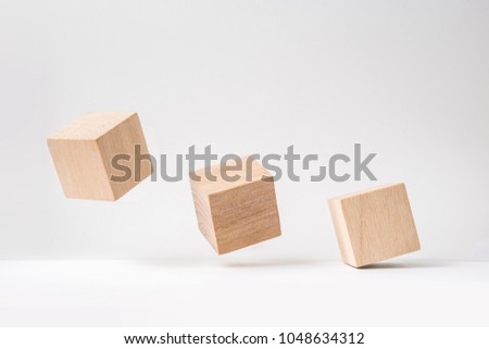 Business and design concept - abstract geometric real wooden cube with surreal layout on white floor background and it's not 3D render. It's the symbol of leadership, teamwork and growth #1048634312
