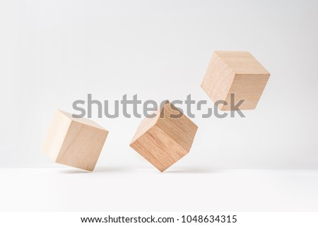 Business and design concept - abstract geometric real wooden cube with surreal layout on white floor background and it's not 3D render. It's the symbol of leadership, teamwork and growth #1048634315