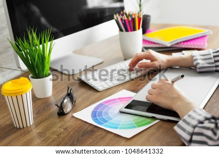Young female designer using graphics tablet while working with computer #1048641332