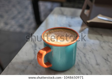 In the cafe : A cup of almond milk cappuccino coffee in orange and blue cup isolated on white table with copy space. #1048650971