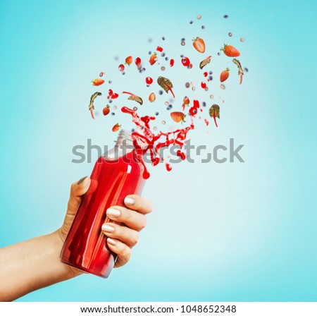Female hand holding bottle with red splash summer beverage: smoothie or juice and berries at blue background.  #1048652348