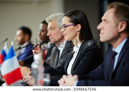 Young female politician in formalwear talking in microphone while making report at political conference #1048667546
