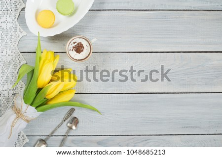 Yellow tulips, chocolate and macarons on a white wooden table #1048685213