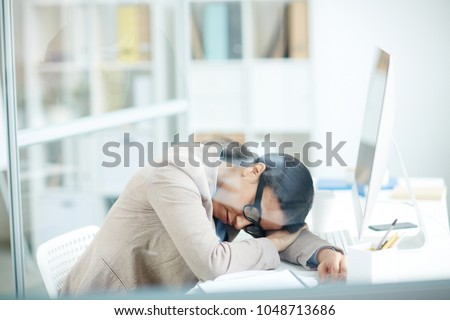Tired businesswoman sleeping at her workplace at office #1048713686