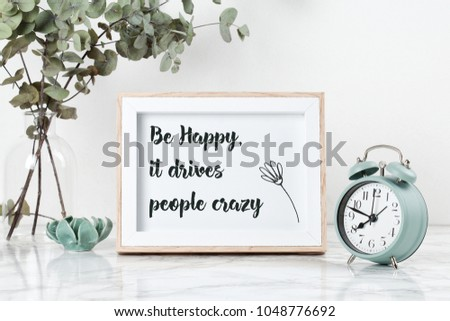 Poster frame with written quote: be happy, it drives people crazy, front view, with decor elements, flowers and blank copy space over the white wall.