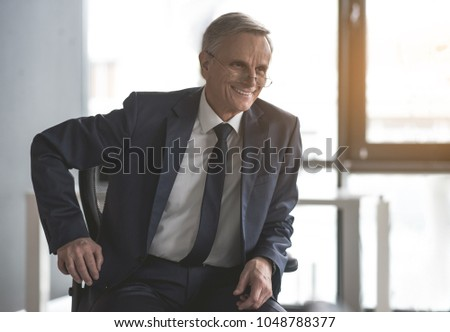 Portrait of beaming old businessman sitting on cozy chair in office. Cheerful employer concept #1048788377