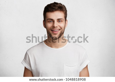 Horizontal shot of handsome young guy with blue eyes and bristle, has positive expression, being praised by someone, dressed casually, isolated over white studio background. Emotions concept #1048818908