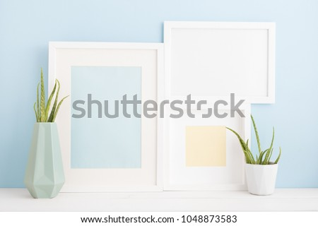 Three photo frames and a house plant. Bright blue color mock up. #1048873583