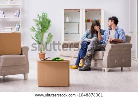 Young family moving in to new apartment after paying off mortgage #1048876001