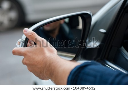 Young human hand is preparing or correct car mirror for the trip or travel from car window. #1048894532