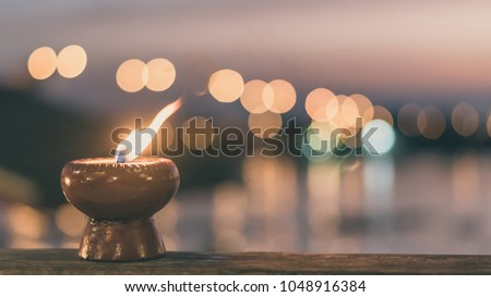 Soul and spirituality abstract concept  for mourning and world human spirit day with warm candle light bokeh illumination, golden sunset sky and reflective river wave background #1048916384
