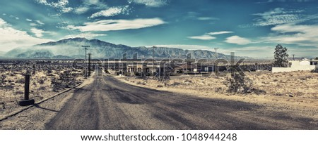 Deserted lonely empty road in San Felipe, Mexico, distant mountain with white summer clouds, few abandoned empty houses in the scorching heat, no cars or people, super wide panorama stitch, Covid-19  Royalty-Free Stock Photo #1048944248