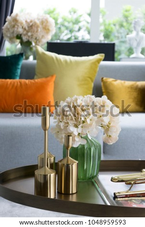 colorful and stylish living room with flower vase and gold trumpet on table. #1048959593