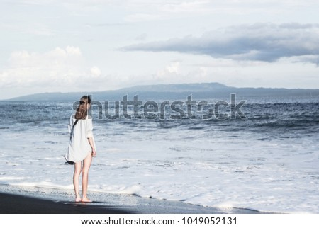 Young woman is walking along the black sand ocean beach. #1049052131