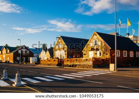 Husavik, Iceland - August 17, 2017: Beautiful view of the historic town of Husavik with traditional houses and traditional fisherman boats lying in the harbor, northern coast of Iceland #1049053175