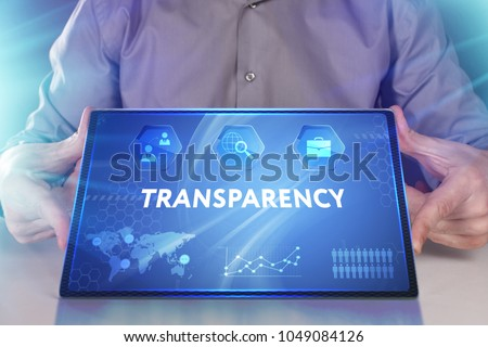 Business, Technology, Internet and network concept. Young businessman working on a virtual screen of the future and sees the inscription: Transparency #1049084126