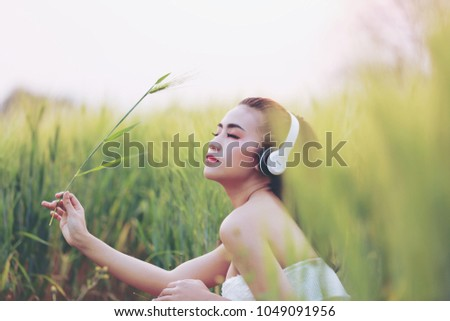Beautiful young girl listening to music on headphones. The girl in the barley farm at sunset time. #1049091956
