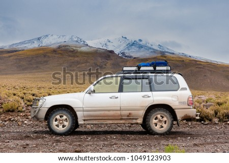 Altiplano, Bolivia, February 2018: offroad vehicle photographed on the gravel road with the  snow covered volcano in the background #1049123903