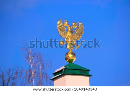 Golden emblem of the Russian Empire against the blue sky. #1049140340