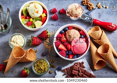 Fresh fruit with scoops of creamy speciality ice cream in assorted flavors with raspberry, berry, blueberry, strawberry, walnut , pistachio, chocolate, sugar cones and a scoop for serving from above #1049230460