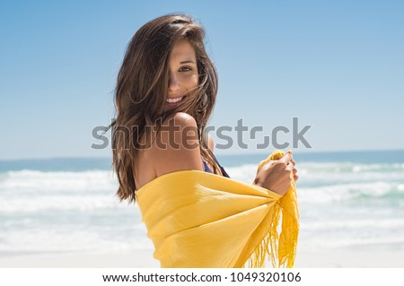 Cheerful young woman in yellow sarong at beach. Happy smiling girl enjoying the beach and looking at camera. Latin tanned woman feeling refreshed in yellow scarf during summer vacation. #1049320106