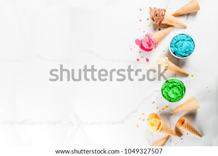 Different homemade melting ice cream in bowls and waffle ice cream cones, white vanilla, orange, pink berry, green, blue, chocolate white marble background  copy space top view