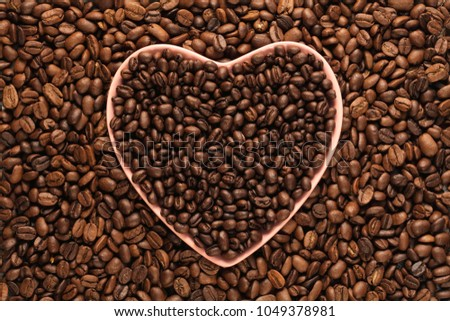 Coffee beans in a heart shaped plate, full frame #1049378981