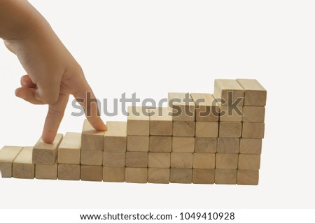 Boy hands, wooden blocks on a white background. Finger gestures up and down with abstract ideas in the world of business competition. #1049410928