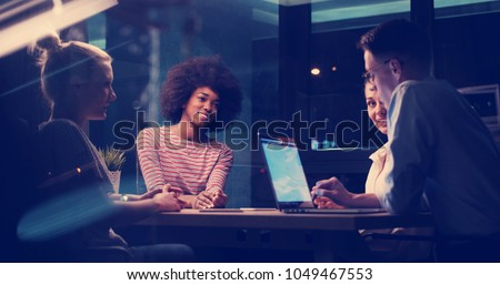Multiethnic startup business team on meeting in modern night office interior brainstorming, working on laptop Royalty-Free Stock Photo #1049467553