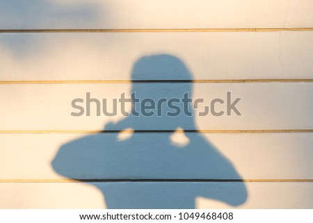 photographer shadow on concrete wall background in the evening time
