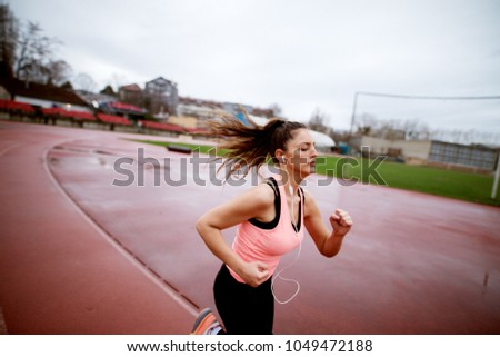Attractive young focused fitness girl sprinting on a track with fluffy hair near the soccer field. #1049472188