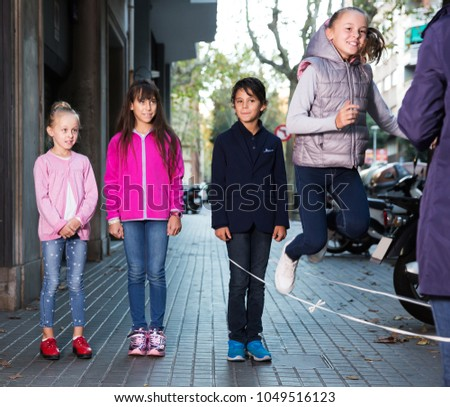 Friendly children play on city sidewalk in autumn city #1049516123