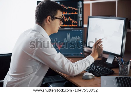 Busy working day. Close-up of young businessman looking at monitor while sitting at the desk in creative office. #1049538932