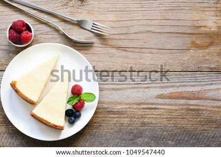 New York cheesecake or classic cheesecake with fresh berries on white plate, wooden table background and copy space for text #1049547440