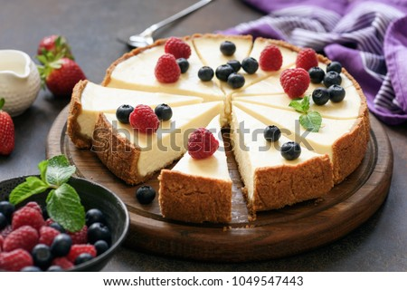 Classic plain New York Cheesecake sliced on wooden board, closeup view, selective focus #1049547443