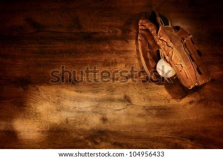 Old worn leather baseball glove and used ball on nostalgic Americana sport wood plank background Royalty-Free Stock Photo #104956433