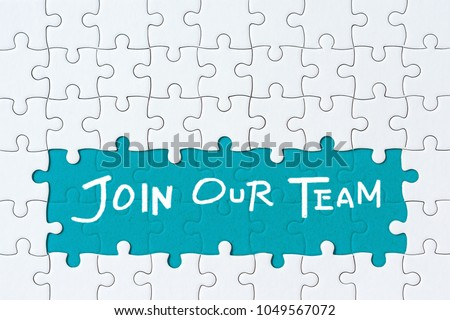 Job recruiting advertisement represented by 'JOIN OUR TEAM' texts on the jigsaw puzzle board. Rows of jigsaw pieces are removed appealing blue green background - metaphor to represent hiring positions #1049567072