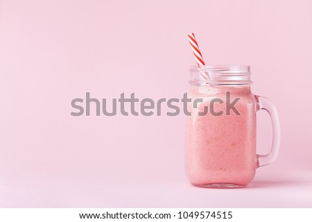 Strawberry smoothie or milkshake in mason jar on pink pastel background. Healthy food for breakfast and snack. #1049574515