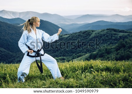 A young girl with a black belt coaches in martial art outdoors. Royalty-Free Stock Photo #1049590979