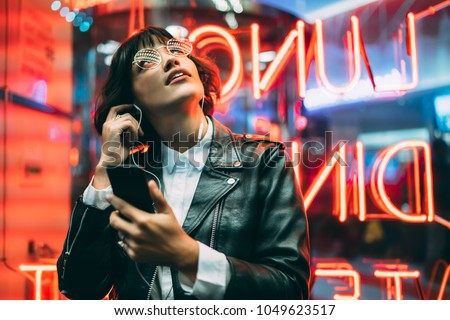 Excited fashion female lover of music dressed in stylish leather jacket listening songs online in earphones connected to smartphone while enjoying night lights and neon illumination in New York City #1049623517