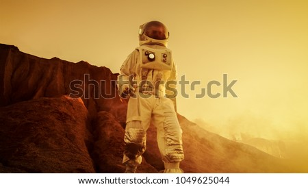 Brave Astronaut Descents from the Mountain on the Alien Red Planet/ Mars. Space Exploration/ Travel, Colonization Concept. #1049625044