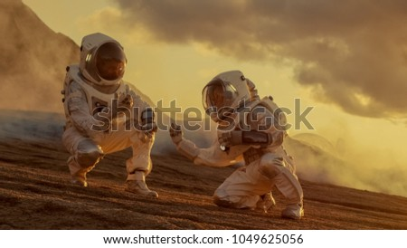 Two Astronauts Collect Soils Samples on Alien Planet, Analyzing Them with Hands Computer. Mars/ Red Planet Manned Expedition.
