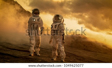 Two Astronauts in Space Suits Confidently Walking on Mars, Exploration Expedition on the Planet's Surface. Red Planet Covered in Rocks, Gas and Smoke. Humans Overcoming Difficulties. #1049625077