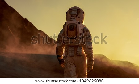 Shot of Astronaut Confidently Walking on Mars. Red Planet Covered in Gas and Smoke. Humans Overcoming Difficulties. Big Moment for the Human Race. #1049625080
