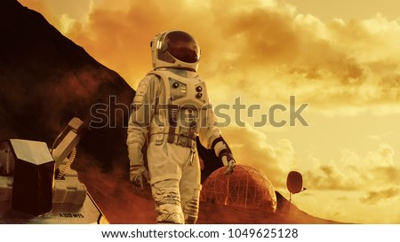 Astronaut on Mars Walking on the Exploring Expedition. In the Background His Base/ Research Station. First Manned Mission To Mars, Technological Advance Brings Space Exploration, Colonization. #1049625128