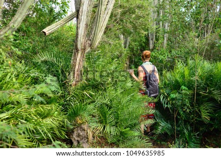 Relaxing tourist on the trekking in the jungle on Dominican Republic. Forest of the Del Este national park close the capital city Santo Domingo #1049635985